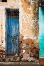 Faded blue door behind locked grate on brick wall with broken pl Royalty Free Stock Photo