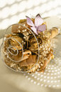 Faded bridal bouquet bunch of dried and dusty flowers for wedding with paper butterffly on a white pillow Royalty Free Stock Photo
