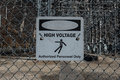 Faded High Voltage Danger Sign on Chainlink Royalty Free Stock Photo