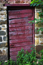 Faded red rustic garden shed door slight off hinges Stock Photos