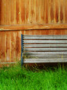 Faded wooden bench, fence, and grass Stock Photos