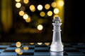 Faint king on blue chessboard with bokeh a Stock Photo