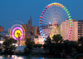 Fair ferris wheel adorned with lights spinning at dusk Stock Photo