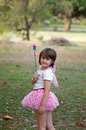 Fairy girl cute and carefree little wearing tutu costume magic wands and wings in a green natural garden Royalty Free Stock Photo