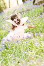 Fairy princess in bluebells a sea of deep the woods floral headdress and backlit by sunlight Stock Photos