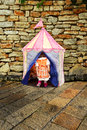 Fairy tale entrance little girl entering into a colorful tent to a world through stone wall Stock Photo