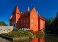 Fairy tale red castle on the lake, with dark blue sky, state castle Cervena Lhota, Czech republic Royalty Free Stock Photo