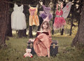 Fairytale princess in the woods reading story book a little child is dressed up as a a with costumes hanging from a clothesline Stock Photos