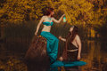 Fairytale woman with a lantern women sitting on snag in the swamp and shines flashlight man Royalty Free Stock Photography