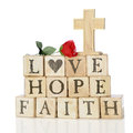 Faith hope and love rustic wood alphabet blocks arranged to say they re topped with a red rose a wood cross on a white Stock Photography