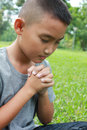 Faith young boy praying with green grass background Royalty Free Stock Images