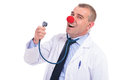 Fake doctor singing a song at his stethoscope with red clown nose Royalty Free Stock Photo