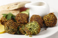 Falafel chickpea balls closeup homemade falafels herbed and spicy one broken open on a plate with egyptian flat bread lemon slices Royalty Free Stock Image