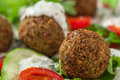 Falafel on salad leaves with tomatoes cucumber and pepper Royalty Free Stock Photography