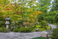 Fall colors in japanese garden early autumn foliage with buddhist stone lantern and winding walking path copy space Royalty Free Stock Image