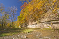 Fall Colors and a Limestone Cliff over a Quiet Stream. Royalty Free Stock Photo