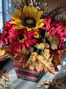 Fall flower arrangement floral arrangment of red yellow and orange flowers sitting on living room table Stock Images