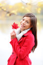 Fall girl holding red autumn leave outside asian woman outdoor portrait in seasonal coat by forest lake female Royalty Free Stock Image