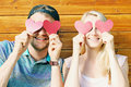 Fall in love concept - young couple holding paper hearts over ey Royalty Free Stock Photo