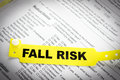Fall risk patient bracelet a yellow on top of a hospital questionnaire paperwork Stock Image