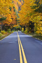 Fall road with car in distance Royalty Free Stock Photography