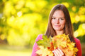 Fall season portrait girl woman with bunch of autumnal leaves happy young colorful in park forest outdoor Royalty Free Stock Images