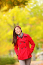 Fall woman walking amongst autumn trees beautfiul laughing young in a trendy red jacket colourful yellow Royalty Free Stock Photo