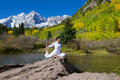 Fall yoga at maroon bells a woman practicing in the scenic in as a backdrop Stock Images