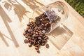 Fallen coffee beans a glass with brown coffe Stock Photo