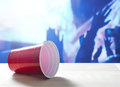 Fallen plastic red party cup on its side on a table. Nightclub or disco full of people dancing on the dance floor. Royalty Free Stock Photo