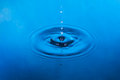Falling drop of water in blue water Royalty Free Stock Photo