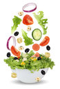 Falling salad in bowl with lettuce, tomatoes, onion and olives Royalty Free Stock Photo