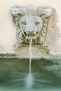 Falling water from lion head fountain Royalty Free Stock Photo