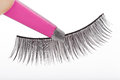 False lashes and pink pincers closeup on white background Royalty Free Stock Photo