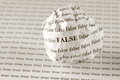 False or true crumpled paper ball with words on background with words sepia Royalty Free Stock Photography
