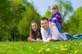 Família feliz que senta se no prado do verão Fotos de Stock Royalty Free