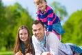 Família feliz que senta se no prado do verão Fotos de Stock