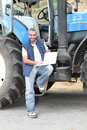 Famer stood by tractor with laptop computer Stock Photo