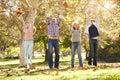 Famiglia che getta autumn leaves in the air Immagine Stock Libera da Diritti