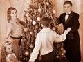 Familia con el árbol de navidad de la danza redonda de los niños. Foto de archivo