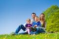 Familia feliz que se sienta en prado del verano Fotografía de archivo libre de regalías