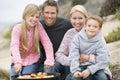 Familie, die einen Strand-Grill genießt Stockfoto