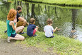 Families with children close to a waterscape with duck on it Royalty Free Stock Photo