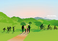 Families in countryside silhouetted enjoying a day out green walking cycling and playing soccer Stock Photography