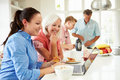 Family with adult children having breakfast together in kitchen looking at laptop screen Royalty Free Stock Images