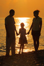 Family against glossing sea. Parents and daughter Stock Photos