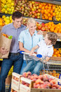 Family against shelves of fruits goes shopping happy father keeps a bag with and son sits in the cart Stock Photo