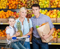 Family against shelves of fruits has shopping goes father keeps a paper bag with and vegetables son hands pineapple Royalty Free Stock Photo