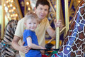Family at amusement park happy smiling son and his handsome father spending fun time together riding merry go round Stock Photo