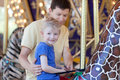 Family in amusement park happy of two at merry go round Stock Photography